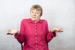 Reife Frauenholding teilt mit einem verwirrten Ausdruck aus Stockfotos