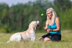 Reife Frauenspiele mit einem Labrador draußen Stockfotografie