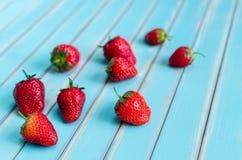 Reife frische Erdbeeren über hölzernem Türkis verlegen Hintergrund lizenzfreie stockbilder