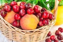 Reife frische organische Pfirsiche, süße Kirschen in einem Fruchtweidenkorb auf hölzernem Gartentisch, Kräuter, Melone, Sommer dr Stockfotografie