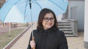Reife gelächelte gehende Frau im Mantel mit Gläsern mit einem Regenschirm stock video footage