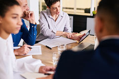 Reife Geschäftsfrau, die ihrem männlichen Kollegen analytische Informationen über Tablette zeigt Stockbilder