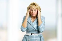 Reife Geschäftsfrau mit Migräne Stockfoto