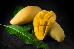 Reife goldene Mangos mit Blatt auf dunklem Hintergrund Lizenzfreie Stockfotos