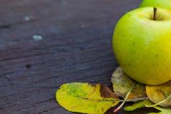 Reife grüne Äpfel auf einem hölzernen Hintergrund mit gelben Blättern Stockfotos