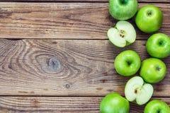 Reife grüne Äpfel und Apfelscheiben auf altem hölzernem Hintergrund Winkel des Leistungshebels Stockfoto