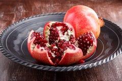 Reife Granatapfelfrucht und -samen auf dunklem Teller lizenzfreie stockbilder