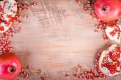 Reife Granatapfelfrucht und -samen auf hölzernem Hintergrund Stockbilder