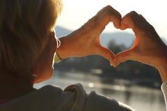 Reife Hände, die Herz gegen Meer und Himmel bilden Lizenzfreie Stockfotos