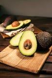 Reife halbierte Avocado auf hölzernem Schneidebrett Lizenzfreies Stockbild