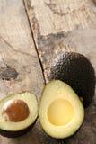 Reife halbierte Avocadobirne auf einer rustikalen Tabelle Stockfotos