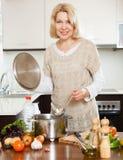 Reife Hausfrau, die Suppe kocht Lizenzfreies Stockbild