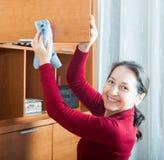 Reife Hausfrau, die zu Hause säubert Stockfotografie