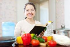 Reife Hausfrau liest Kochbuch für Rezept Stockbild
