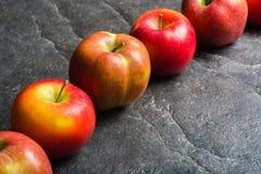 Reife Herbstäpfel rot und gelb auf einem schwarzen Steinhintergrund vom Schiefer Ernten Vitamine sind für Gesundheit gut lizenzfreies stockfoto