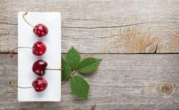 Reife Kirschen auf Holztisch Stockfotos