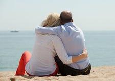 Reife Liebhaber, die auf Strand sitzen Stockfotografie