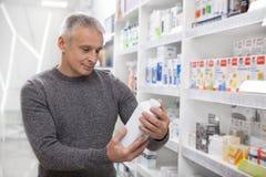 Reife Mannkaufenmedikationen am Drugstore stockfoto