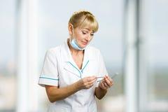 Reife medizinische Ärztin, die auf Thermometer schaut Lizenzfreie Stockbilder