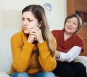 Reife Mutter, die um Verzeihen von der erwachsenen Tochter bittet Lizenzfreies Stockfoto
