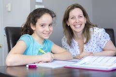 Reife Mutter, die zu Hause ihrem Kind mit Hausarbeit hilft lizenzfreies stockfoto