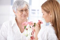 Reife Mutter und junge Tochter mit Blüte Stockbild