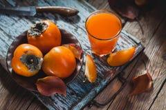 Reife orange Persimonefrucht und Persimoneblätter in einer braunen Platte auf einem braunen Holztisch stockfotos