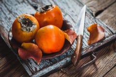 Reife orange Persimonefrucht und Persimoneblätter in einer braunen Platte auf einem braunen Holztisch stockbilder