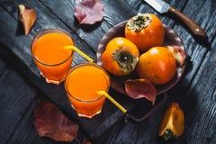 Reife orange Persimonefrucht und Persimoneblätter in einer braunen Platte auf einem schwarzen Holztisch lizenzfreie stockfotos