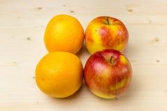Reife Orangen und Äpfel auf einem hölzernen Hintergrund Stockbild