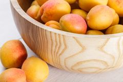 Reife organische Aprikosenfrüchte in der hölzernen Schüssel der Esche lizenzfreie stockfotografie