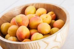 Reife organische Aprikosenfrüchte in der hölzernen Schüssel der Esche stockfotos