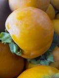 Reife organische Persimone trägt in einem Stapel am lokalen Landwirtmarkt Früchte Persimonehintergrund Stockbilder