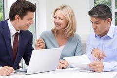 Reife Paar-Sitzung mit Finanzberater zu Hause lizenzfreies stockfoto
