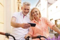 Reife Paare auf Fahrrädern draußen Stockfotografie