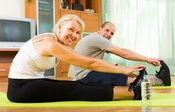 Reife Paare, die Übungen tun Stockfotos