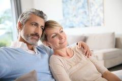 Reife Paare, die auf Couch sitzen Stockfotos