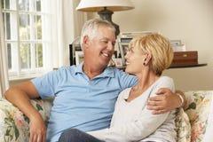 Reife Paare, die auf Sofa At Home Together sitzen stockbilder