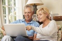 Reife Paare, die auf Sofa At Home Using Laptop sitzen stockfotografie