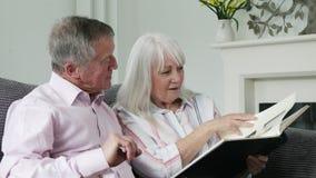 Reife Paare, die auf Sofa And Looking At Foto-Album sitzen stock footage