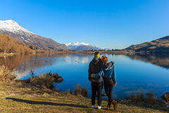 Reife Paare, die den See bereitstehen lizenzfreies stockbild