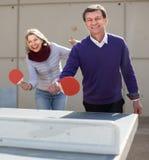 Reife Paare, die draußen Tischtennis spielen Stockfoto