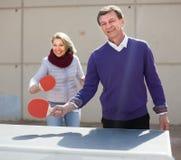 Reife Paare, die draußen Tischtennis spielen Stockbild