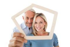 Reife Paare, die durch Rahmen schauen Lizenzfreies Stockfoto