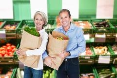 Reife Paare, die Einkaufstüten halten lizenzfreies stockfoto