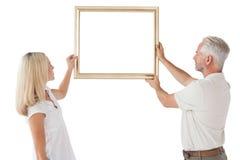 Reife Paare, die herauf Bilderrahmen hängen Stockbild