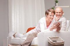 Reife Paare, die lustige Sachen auf einer Tablette aufpassen Lizenzfreies Stockfoto