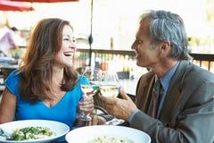 Reife Paare, die Mahlzeit Restaurant am im Freien genießen Stockbild