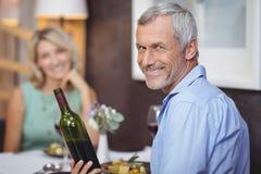 Reife Paare, die Mahlzeit und Rotwein essen Stockfotos