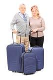 Reife Paare, die mit ihrem Gepäck aufwerfen Stockbilder